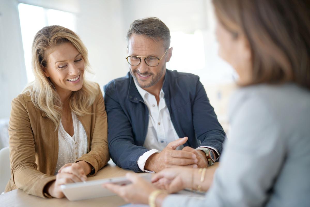 aides à l'achat immobilier neuf - Un couple en rendez-vous à la banque pour une demande de prêt immobilier