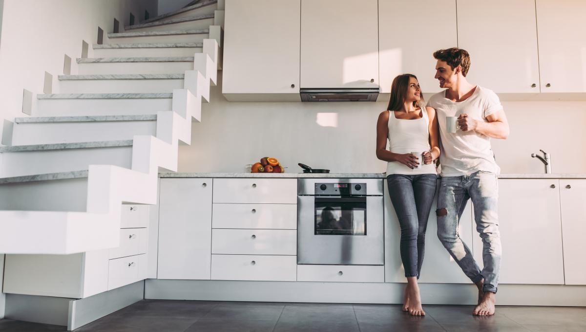 taux de crédit immobilier bordeaux - Un couple se tenant dans une cuisine moderne dans un logement neuf