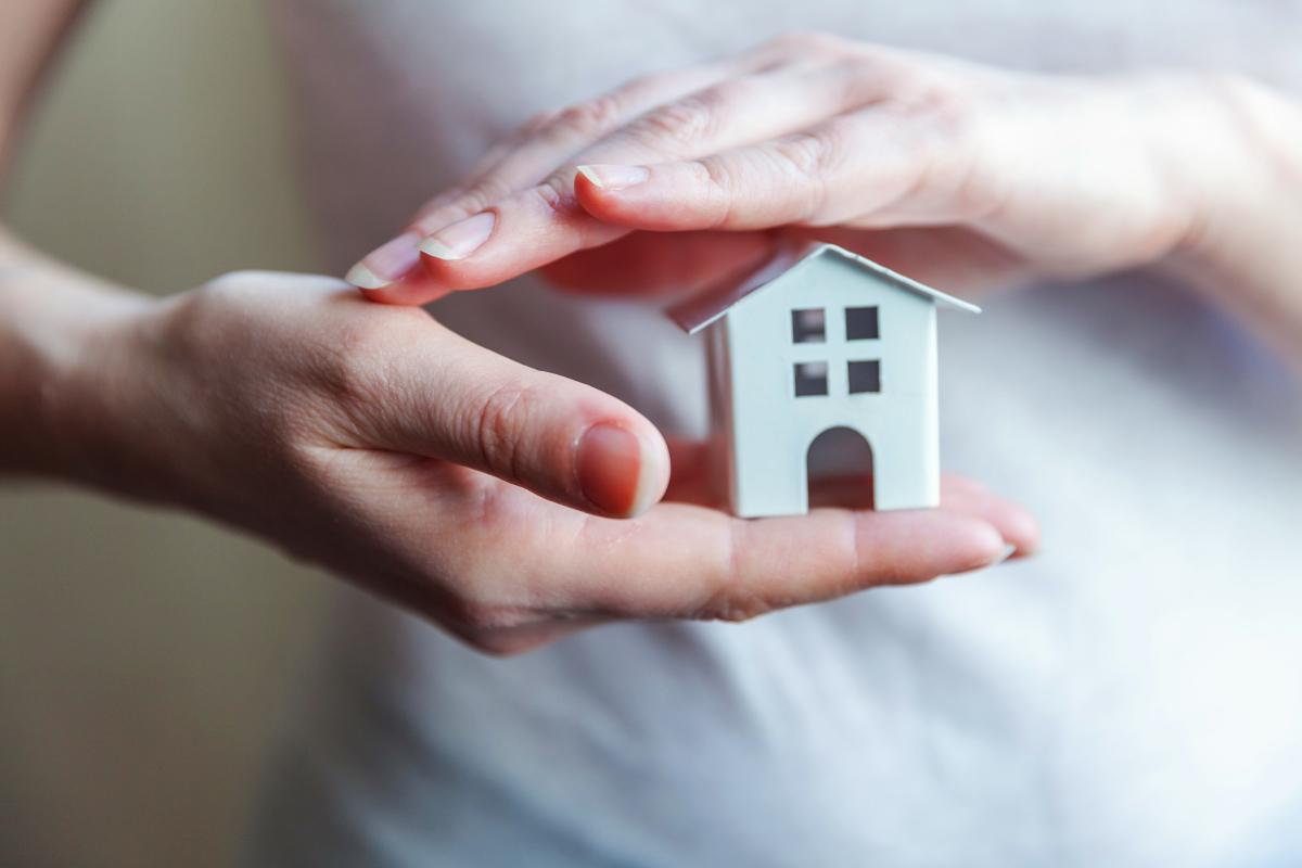 Agence de gestion locative à Bordeaux – Deux mains qui entourent une maison miniature blanche