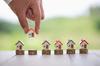 Agence de gestion locative à Bordeaux – Main posant des figurines de maisons sur des piles de pièces de monnaie
