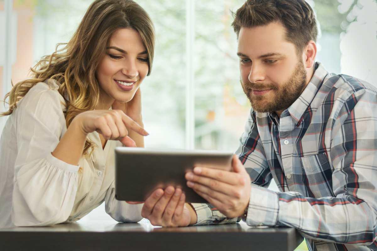 investir dans l'immobilier - Un couple navigue sur internet via une tablette numérique