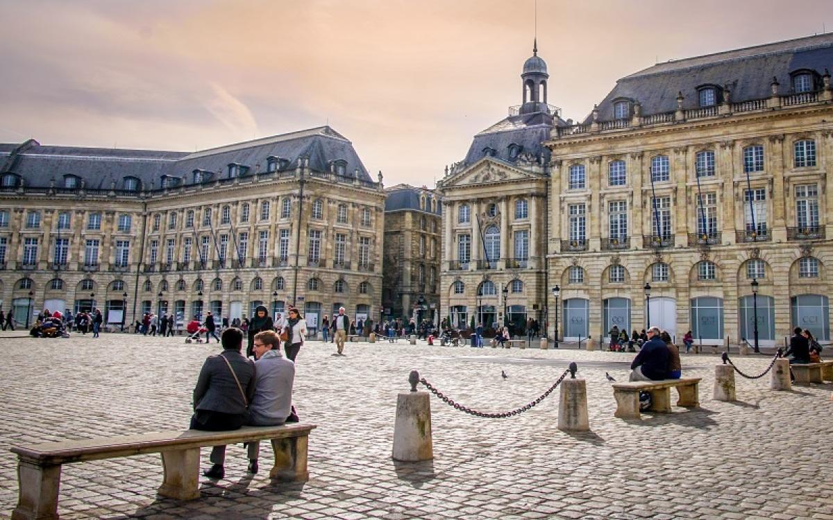 Couple assis sur un banc sur la Place de la Bourse à Bordeaux
