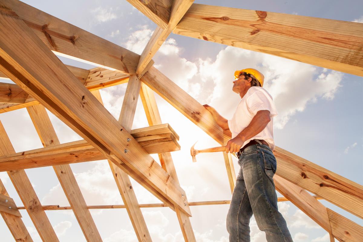 construction neuve - un ouvrier sur un chantier de construction installant le toit d'une maison