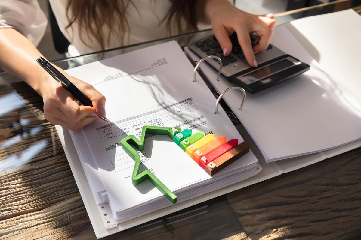 Immobilier écologique - Femme calculant ses factures d'électricité et la performance énergétique