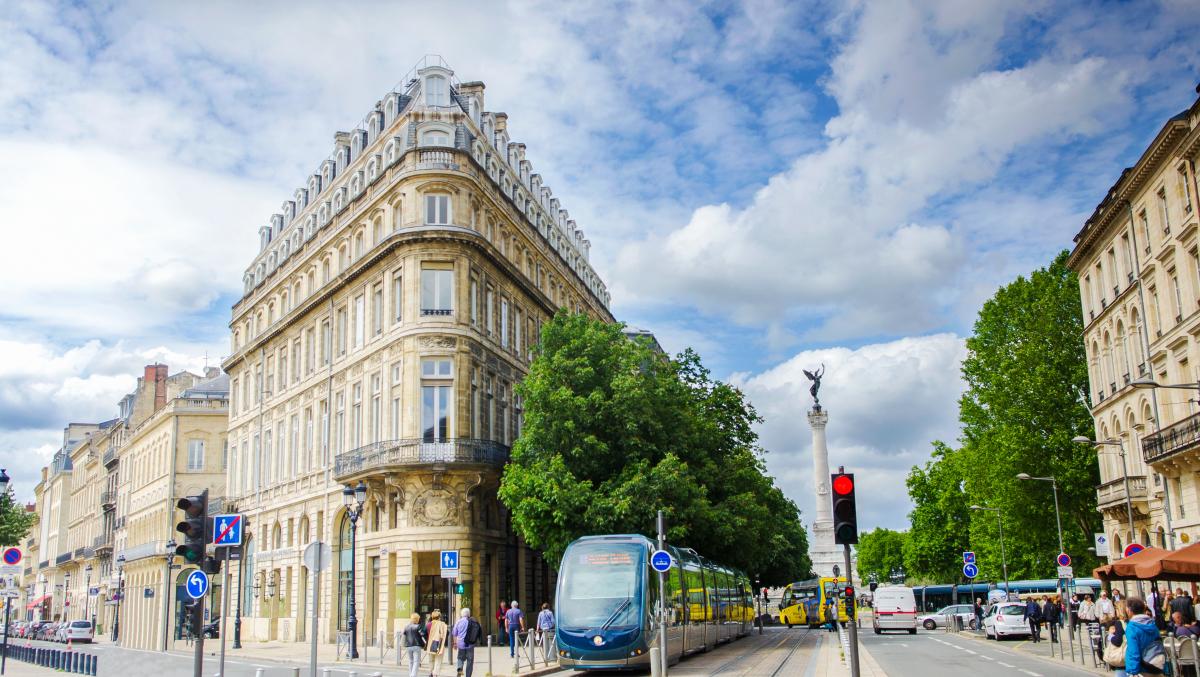 Loi Pinel Bordeaux – Tram passant au pied d'un immeuble ancien dans une rue du centre de Bordeaux+