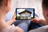 Pass sanitaire et location – Couple en gros pan de dos regardant une maison sur tablette