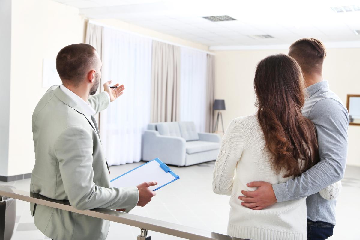 Pass sanitaire et location – Jeune couple visitant un bien avec un agent immobilier